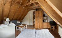 Im Dachgeschoss befindet sich ein Doppelbett sowie eine Schlafcouch mit Sitzgruppe. Hinten im Bild die Tür zum zweiten Schlafzimmer. - Bild 11: Ferienhaus BUTEN gemütliche Doppelhaushälfte mit Terrasse und Garten