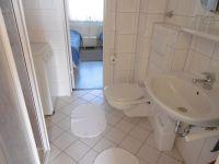 Das weiß geflieste Badezimmer mit geräumiger Duschkabine. Auch eine Waschmaschine für den kleinen Waschtag zwischendurch steht bereit. Eine Verbindungstür zum Schlafraum nach Osten öffnet den Blick auf die Ostsee. - Bild 14: Großzügige Ferienwohnung mit Meerblick im Ostseebad Hohwacht