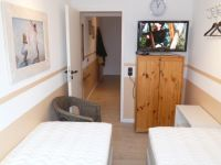 Im Schlafzimmer stehen 2 Einzelbetten, ein Kleiderschrank und ein Flachbild-TV. - Bild 11: Groemitz-Villa am Meer - Seeblick Ferienwohnung