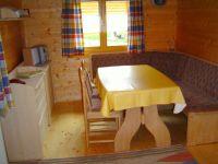 Ausziehbarer Eßtisch mit Eckbank und Stühlen. Links ein Sideboard mit Mini-Stereoanlage. - Bild 2: Urlaub im Blockhaus - Ruhe und Natur für Mensch und Hund
